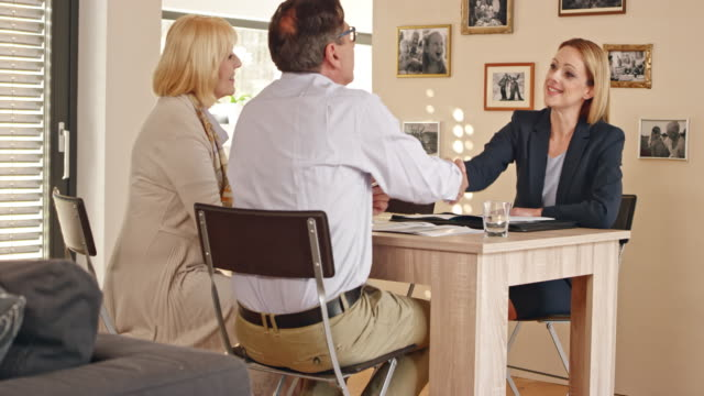insurance agent shaking hands with a senior couple at a meeting in their home - home insurance stock videos & royalty-free footage