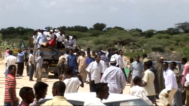 Insurgency brings bloodshed and chaos to Mogadishu EXT Crowd of people on foot and arriving in trucks for funeral Body of journalist Mahed Ahmed Elmi...