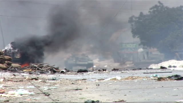insurgency brings bloodshed and chaos to mogadishu somalia mogadishu ext clouds of smoke sandbags and piles of burning debris at roadside as man runs... - cenere video stock e b–roll