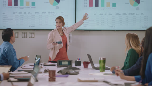 intelligent businesswoman explains data graphs as she leads a team business meeting, coworkers take notes and ask questions - global communications stock videos & royalty-free footage