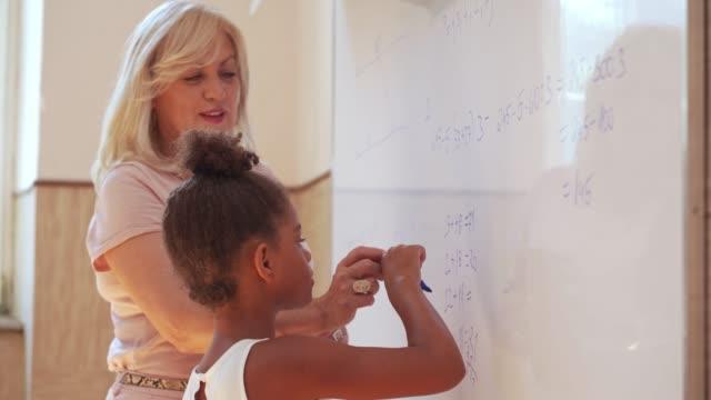 stockvideo's en b-roll-footage met intelligente vrouwelijke elementaire student die wiskunde op een witte raad met een leraar doet - plusteken