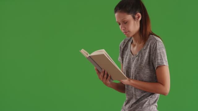 Intelligent white girl reading literature book standing indoors green screen