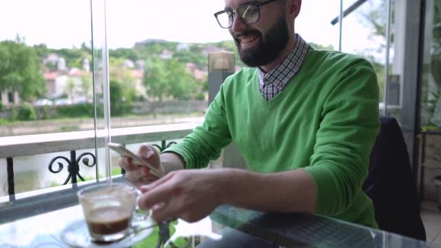 vídeos y material grabado en eventos de stock de joven inteligente sentado en el café de la calle - mesa baja de salón