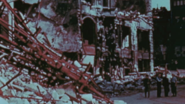 intense destruction from air raids, with crumbling buildings and pedestrians passing / berlin, germany - bombe stock-videos und b-roll-filmmaterial
