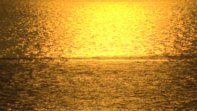 Intense golden sunlight lights up the Tyrrhenian Sea at dawn.