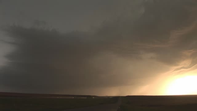 intense lightning strikes near the horizon at golden hour. available in hd. - golden hour stock videos & royalty-free footage