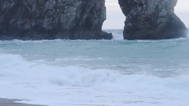intense ocean waves splashing at the bottom of durdle door in lulworth cove, dorset, england - beautiful nature scenery - medium shot - natural arch stock videos & royalty-free footage