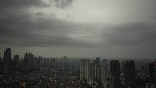 vídeos y material grabado en eventos de stock de intense storm clouds fill the sky in jakarta and block out all sunlight in the indonesia cityscape - yakarta