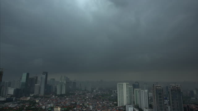 intense storm clouds in the gray sky above the cityscape and skyscrapers in jakarta, indonesia - jakarta stock videos & royalty-free footage