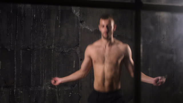 Intense training of muscular young man exercising with jumping rope