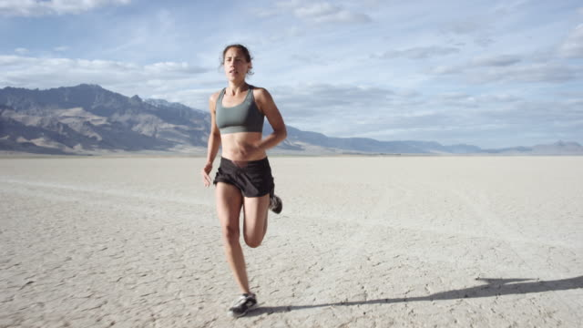 slo mo : intense woman running through desert - running stock videos & royalty-free footage