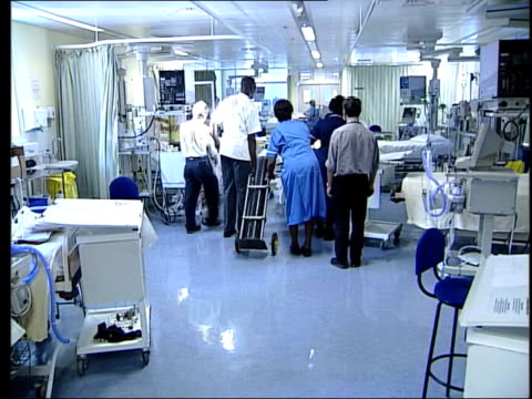 intensive care beds shortage lib patient in bed wheeled along in intensive care ward followed by oxygen cylinder wheeled along on trolley monitor... - oxygen cylinder stock videos & royalty-free footage