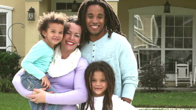 Interacial family with two children in front of house