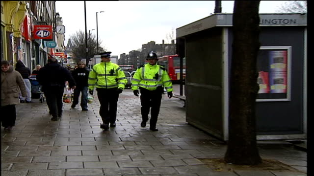 interactive cctv control hubs introduced in islington two male police officers towards on street past emergency help point terminal track - islington stock-videos und b-roll-filmmaterial