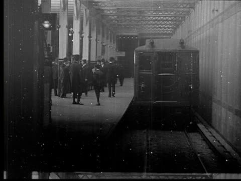 1905 b/w ts ws interborough subway train entering grand central station, men walking around / new york, new york, usa - metropolitana di new york video stock e b–roll