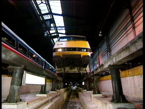 intercity train comes into station platform and passes over camera showing under carriage. - 1989 stock videos and b-roll footage