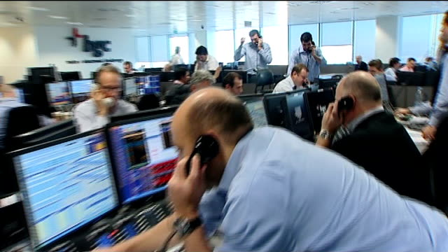 vídeos y material grabado en eventos de stock de interest rate cut stems stock market fall; int monitor in trading room showing ftse 100 index with lots of shares in red sequence dealers working... - negociador bursátil