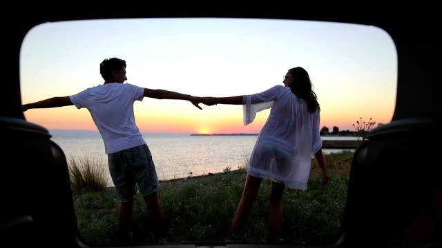 interessante giovane coppia in vacanza. mare e tramonto sullo sfondo. - young couple video stock e b–roll