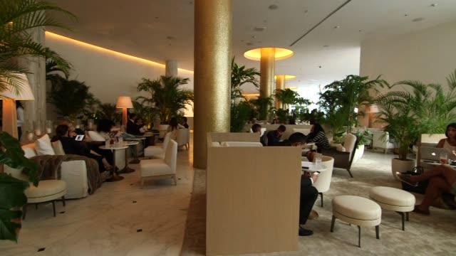 stockvideo's en b-roll-footage met interior and exterior shots of lounges in hotels in miami, florida on 01-26-15, wide shots of a spacious hotel lounge filled with customers... - achterover leunen
