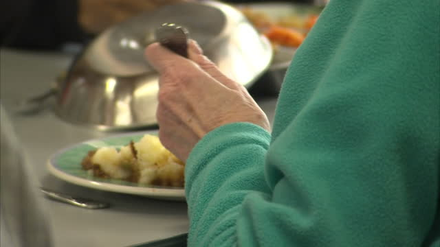 interior anon anonymous shots of older elderly people in a care home at meal time being served food by anon care workers and eating dinner eating... - adding salt stock videos and b-roll footage