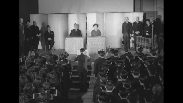 interior auditorium emperor hirohito and empress nagako up steps to stage and take seats in behind tables / they stand behind tables / very blurred... - japanese school uniform stock videos & royalty-free footage