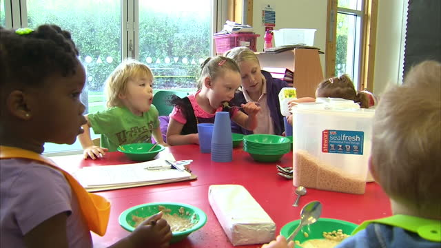 interior children sat around table eating breakfast cereal in nursery New childcare reforms to be introduced on September 02 2013 in UNSPECIFIED