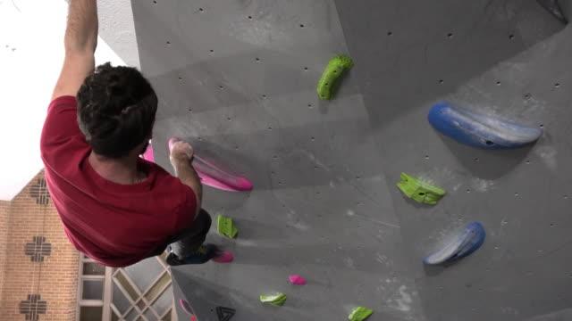 innenkletterwand junge männer trainieren amateursport - kletterwand kletterausrüstung stock-videos und b-roll-filmmaterial