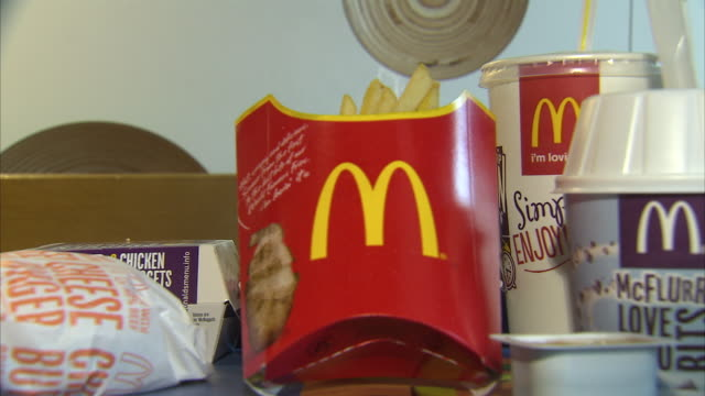 interior close up of some menu items from mcdonald's, including a big mac, fried, chicken nuggets, cheeseburger, mcflurry and a drink. this clip also... - menu stock videos & royalty-free footage