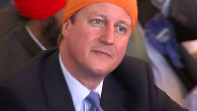 interior close up shots david cameron prime minister leader of conservative party wearing small orange turban sitting among sikhs on floor listening... - turban stock videos & royalty-free footage