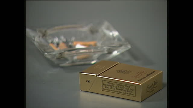 interior close up shots of a gold benson hedges cigarette packet and ashtray and a warning note on the packet smoking when pregnant can injure your... - tobacco product stock videos & royalty-free footage