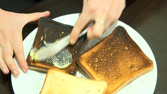Interior close up shots of an anonymous person spreading butter onto a slice of burnt toast and eating it on January 23 2017 in England