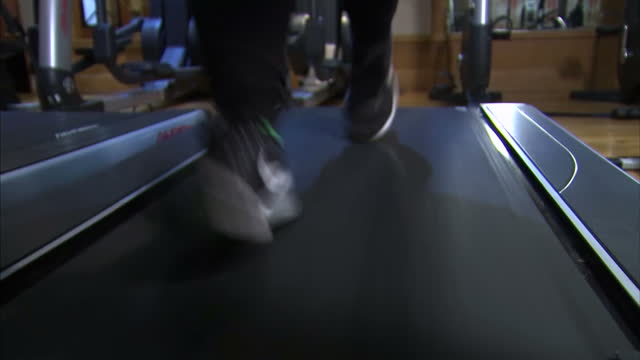interior close up shots of an anonymous person's feet whilst running on a treadmill in december 2016 in england - ungesund leben stock-videos und b-roll-filmmaterial