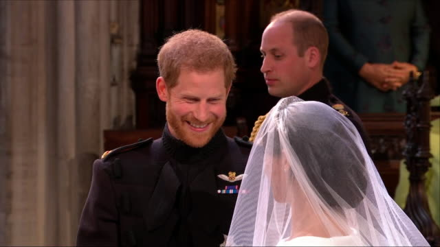 vídeos de stock e filmes b-roll de interior close up shots of prince harry and meghan markle gazing at each other, smiling and giggling as they meet at the alter inside st george's... - casamento