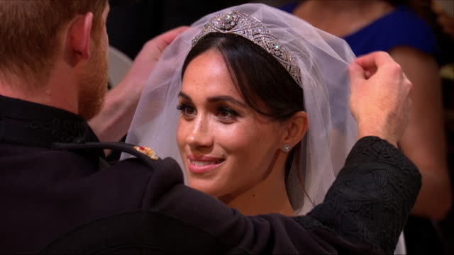 Interior close up shots of Prince Harry lifting the veil of Meghan Markle as they stand at the alter during their wedding ceremony inside St George's...