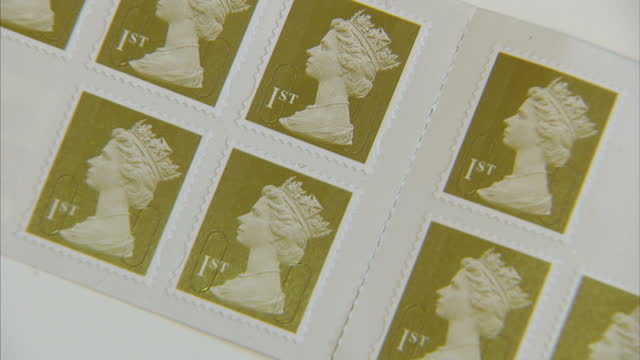 vídeos de stock, filmes e b-roll de interior close up shots various royal mail stamps including first class second class for worldwide europe interior close up shots london 2012... - selo postal