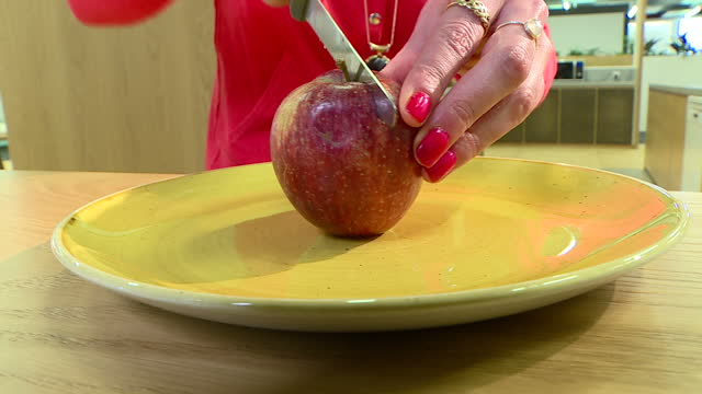 interior closeup shot of an anonymous woman cutting an apple in half on a plate>> on february 23 2017 in london england - cut video transition stock videos & royalty-free footage