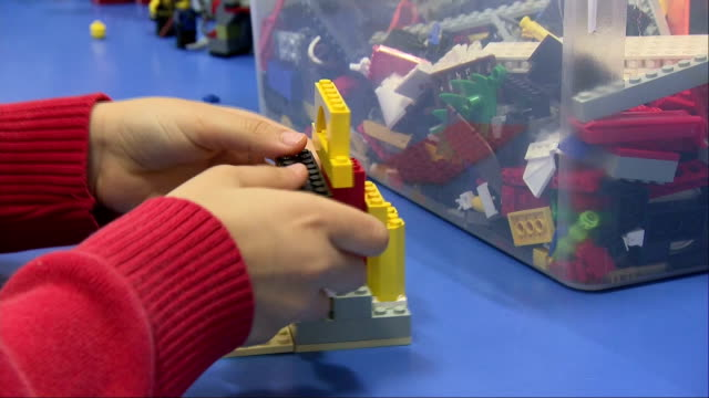 Interior closeup shots of anonymous schoolchildren playing with LEGO blocks in a classroom searching through storage boxes and connecting bricks to...