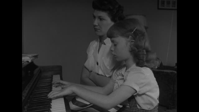 interior dale sprout home: wife iva sits at piano with daughter, son sits on floor playing with a ball, usaaf wwii veteran dale reads in chair / vs... - klippe stock-videos und b-roll-filmmaterial