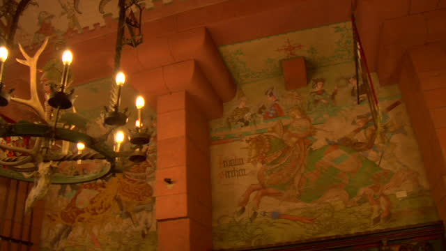 interior decor of a medieval castle banquet hall featuring paintings and candelabras with antlers and animal fur. - banquet hall stock videos & royalty-free footage