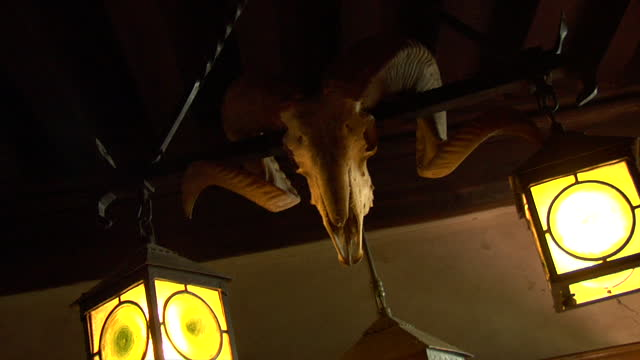 interior decor of a medieval castle banquet hall featuring the ram's head skull with curved horns hanging from a candelabra. - banquet hall stock videos & royalty-free footage