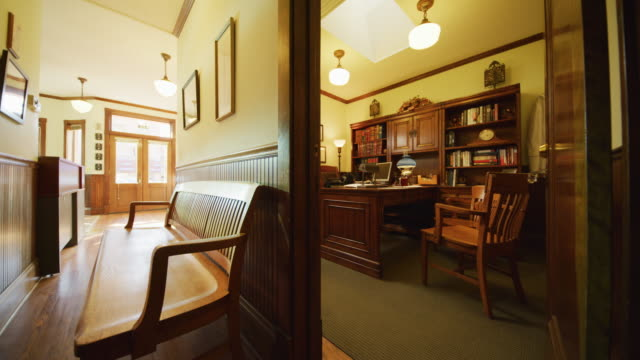 interior doorway of an empty office featuring an oak desk chairs and bookcases in a small town doctor's or insurance office; camera dollies past doorway to focus on empty wooden bench in waiting room. - office doorway stock videos & royalty-free footage