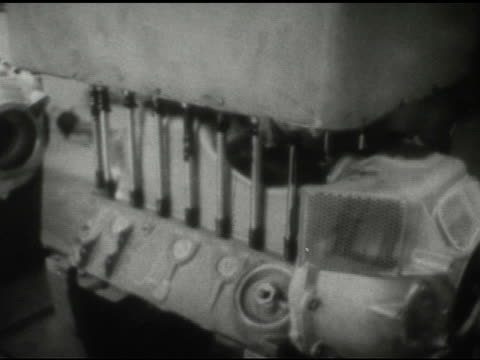 / interior factory, man operates machine that transports partially assembled engine / machine as it releases / partially assembled engines move along... - 1959 stock videos & royalty-free footage