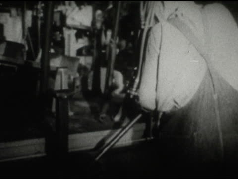 / interior factory, man pushes lever on assembly line / men on hands and knees clean machine on january 01, 1959 - man and machine stock videos & royalty-free footage