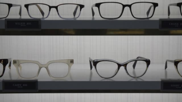 interior footage of a warby parker lens store with many glasses on display on greene street in new york ny on january 31 2017 shots wide tilt down of... - brille stock-videos und b-roll-filmmaterial