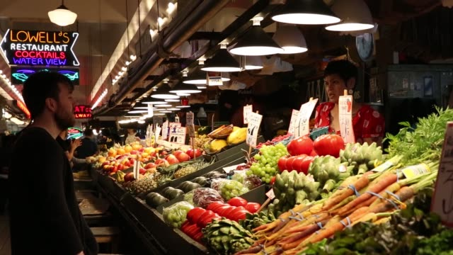 Interior footage of Pike Place Market as produce is sold in Seattle WA on May 18 2017 Shots interior shot of marketplace as people walk by customer...