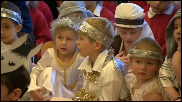 interior footage showing various children dressed for nativity play and parents seated ahead of play. shows prince charles, prince of wales arrving... - キリスト降誕点の映像素材/bロール