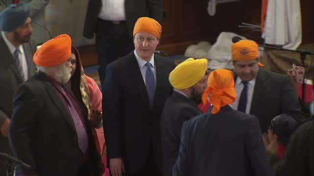 interior high shots prime minister david cameron wearing orange turban inside guru nanak darbar gurdwara temple taking part in vaisakhi festival on... - turban stock videos & royalty-free footage