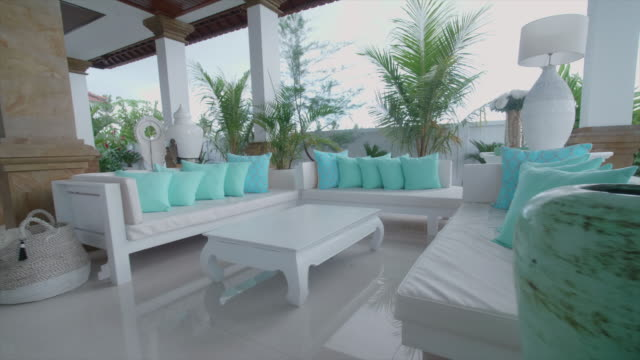 interior inside a villa resort hotel living room with green pillows in exotic tropical bali, indonesia. - 高級ホテル点の映像素材/bロール