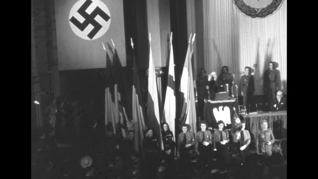 vs interior large auditorium nazi swastikas on banners flags / vs young women in nazi uniforms in line with german nazi flags in front of stage... - nazi swastika stock videos and b-roll footage
