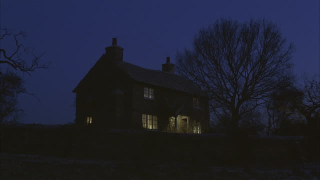 Interior lights illuminate the windows of a two story farmhouse.